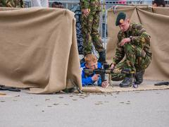 Children play with weapons on army day Stock Photos