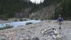 Canada Alberta Banff Bow Falls man hikes near stream 10 Stock Footage