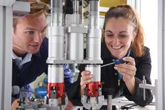 Engineer and apprentice working on machine in factory Stock Photos
