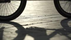 bicycle wheels passing on the sidewalk in the evening, in front of the sun - stock footage