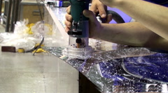 Sawing mirrored plastic using an electric grinder. Closeup. Stock Footage