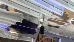 Mounting of the suspended designed luminaire. Drilling mounting holes. Stock Footage