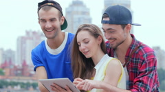 Friends help the girl deal with the tablet Stock Footage