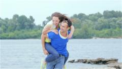 Girl guy jumped on his back and they run on the beach. Slow Motion. - stock footage