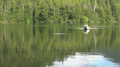 Stock Video Footage of Canada British Columbia Echo Lake canoe approaches on calm water