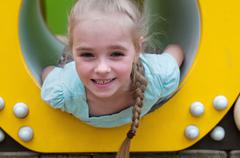 Adorable young girl sitting in crawl tube Stock Photos