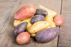 Group of fingerling potatoes on wooden table Stock Photos