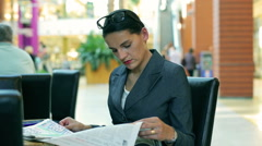 Occupied businesswoman reading newspaper in the restaurant Stock Footage