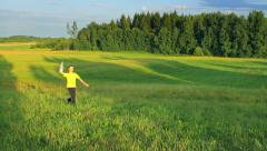 Young boy runs in the field and throws a paper airplane, dream, freedom Stock Footage