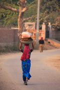 local woman in traditional dress carrying bundle on her head, sawai madhopur, - stock photo