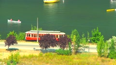 Historical electric tram light rail transit passenger car travels along lake Stock Footage