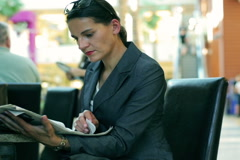 Businesswoman reading newspaper in restaurant in modern place Stock Footage