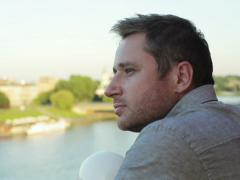 Man standing on terrace and drinking beer next to the river Stock Footage