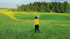 Young boy running in the field, a paper airplane, future, childhood, dream Stock Footage