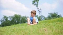 Little Boy Sittin On Green Hill Stock Footage
