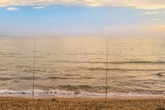 Beautiful sunset over the tyrrhenian sea and two rods Stock Photos