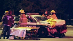 Firemen sawing off car windshield during extrication process Stock Footage
