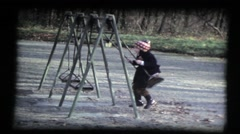 Girl on a swing in park, outside, winter, sequence, vintage 8mm film Stock Footage