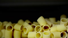 Raw pasta striking and falling down into a machine. Stock Footage