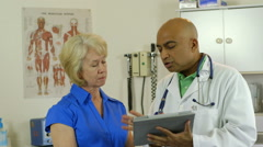 doctor showing paitent something on a tablet pc - stock footage