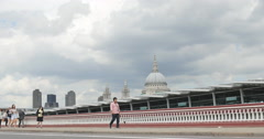 Pedestrians walk over bridge, St Pauls background 4K Stock Footage