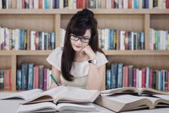 beautiful student studying in the library - stock photo