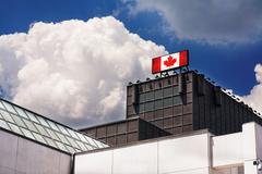 Mainostaulu kyltti kanadan lippu päälle rakennuksen vastaan bl Kuvituskuvat