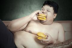 fat man eating two hamburgers while watching tv at home - stock photo