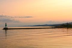 Calm waters at sunset on a harbor breakwater Stock Photos