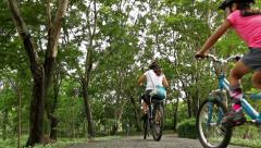 Healthy diverse family bike riding together in park, Pan shot Stock Footage
