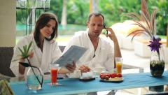 Couple with cellphone and magazine sitting by table in luxury villa HD Stock Footage