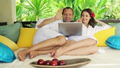Couple video chat on laptop, relaxing on gazebo bed in garden HD Stock Footage