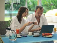 Couple shopping online on laptops by the table in luxury villa NTSC - stock footage
