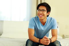 happy asian man sitting on the bed at home - stock photo