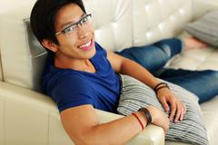 Smiling asian man relaxing at home on the sofa Stock Photos