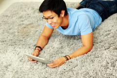 happy asian man lying on the carpet with tablet computer - stock photo