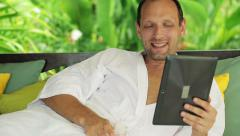 Man chatting on tablet computer during relax on gazebo bed in garden HD Stock Footage