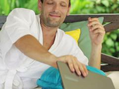 Man with laptop having break for coffee and relax on gazebo bed NTSC Stock Footage