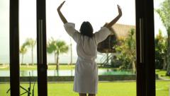 Woman in bathrobe stretching on patio in luxury villa HD Stock Footage