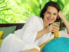 Woman raising toast, drinking cocktail on gazebo bed in garden NTSC Stock Footage