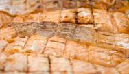 Stock Photo of grilled salmon pieces on white plate at green grass