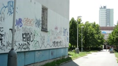 Graffiti on the wall of a block of flats with the street (park with building) Stock Footage