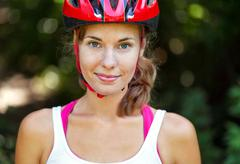 portrait of happy young cyclist in sport clothes and helmet. - stock photo