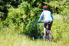 young woman with mountain bike outdoors. - stock photo