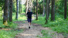 Hiker with walking sticks in the forest trail - stock footage
