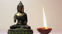 Statuette of Buddha and a burning candle. Stock Footage