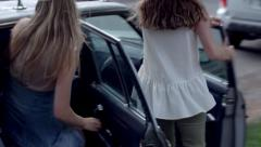 4 Excited Teenage Girls Run Down Sidewalk And Pile Into Their Friend's Car Stock Footage