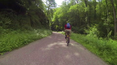 Biker is riding downhill on a street Stock Footage