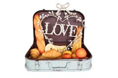 Bread set in travel luggage with love on white background Stock Photos