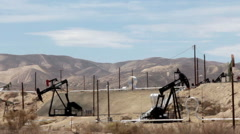 Oil wells pumping in the hot, arid desert providing crude oil to the nation Stock Footage